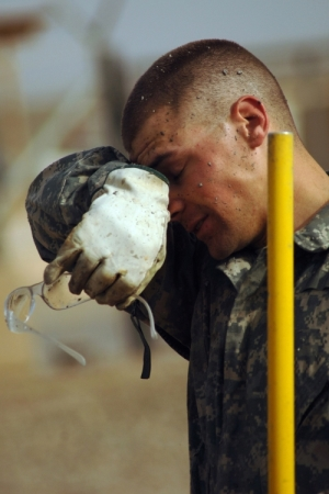 Soldier wiping sweat from his brow